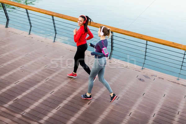 Twee jonge vrouwen lopen promenade rivier ochtend Stockfoto © boggy