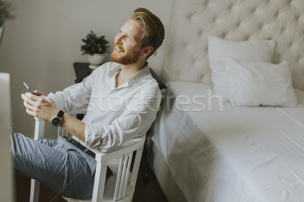 Handsome redhair man writes a message on the phone Stock photo © boggy