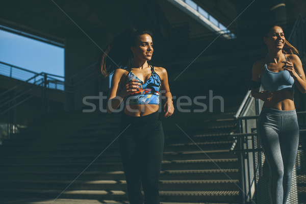 Two young women running in urban enviroment Stock photo © boggy
