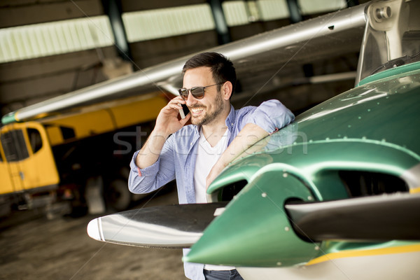 Handsome young pilot checking airplane in the hangar and using m Stock photo © boggy