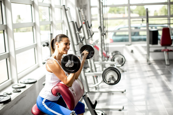 Focused young beautiful woman lifting weights in a gym Stock photo © boggy