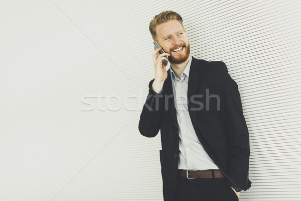 Modern redhair man with mobile phone standing in the office Stock photo © boggy