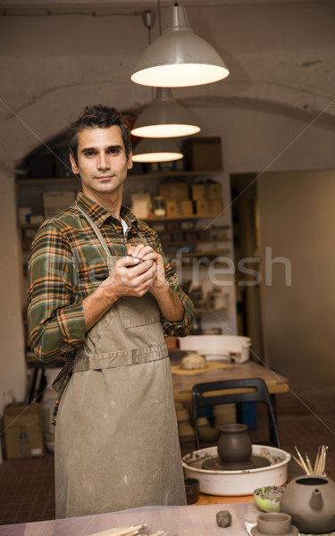 Handsome young man in pottery workshop holding clay Stock photo © boggy