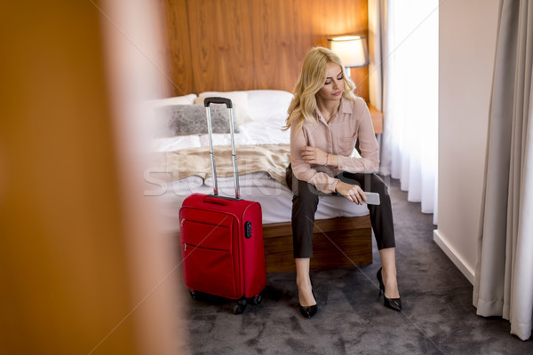 Stock photo: Young businesswoman arrives in a hotel room with red suitcase an