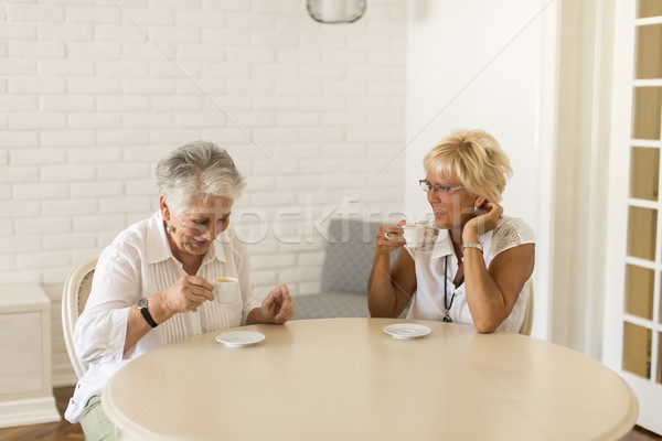 Stock photo: Two older women drinking coffe at home and talking