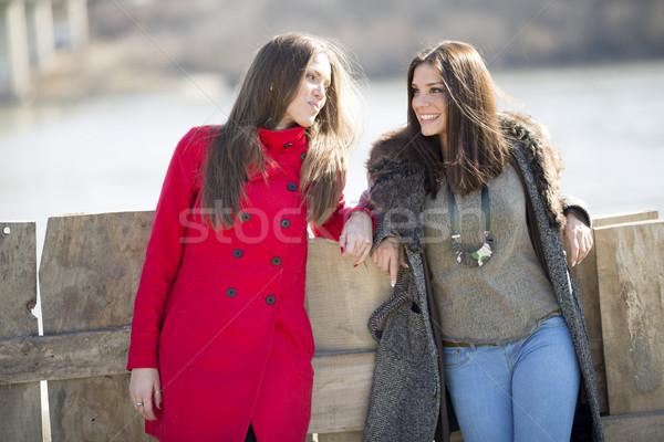 Foto stock: Dois · mulheres · jovens · em · pé · cerca · um · vermelho