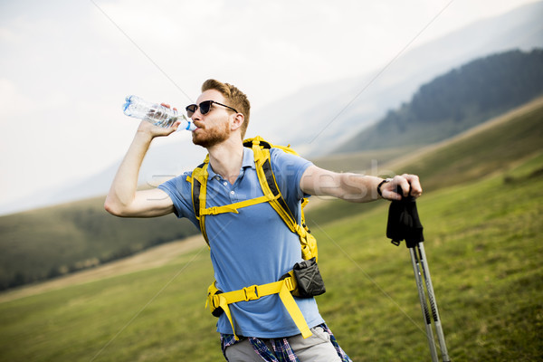 Young hiker stopped and drink water from a bottle Stock photo © boggy