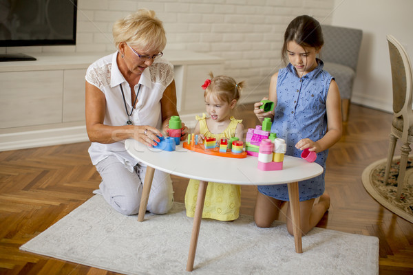 Grandmother playing with little granddaughters in the room Stock photo © boggy