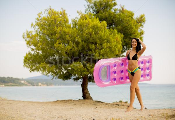 Jonge vrouw matras strand mooie water meisje Stockfoto © boggy