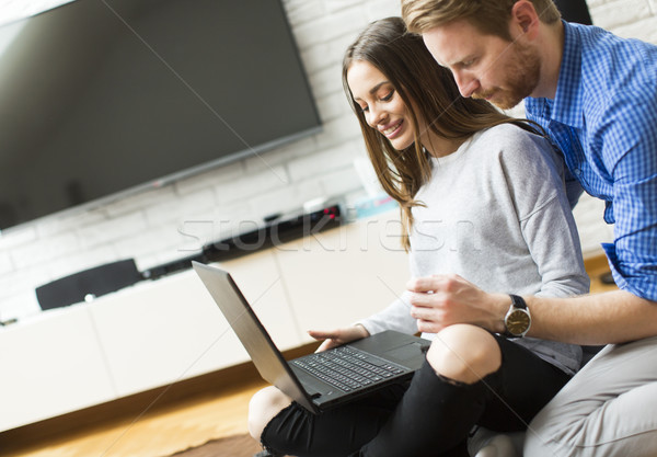Young couple sitting while using a laptop Stock photo © boggy
