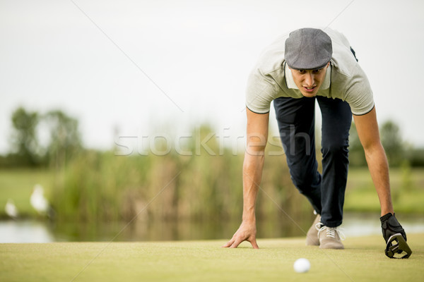 Young man looking at ball while crouching on golf course Stock photo © boggy