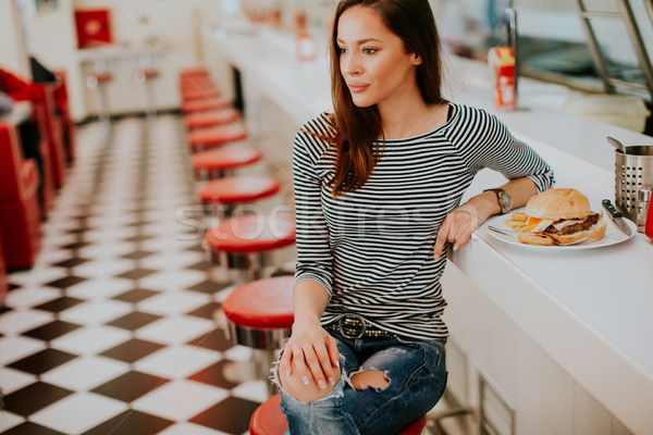 Pretty young woman sitting in the diner Stock photo © boggy