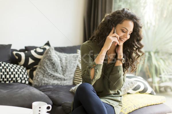 Mulher bonita cabelos cacheados sessão sofá quarto mulher jovem Foto stock © boggy