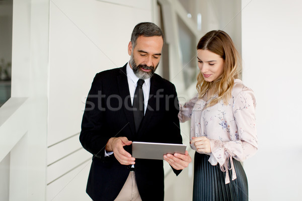 Middle-aged businessman and young businesswoman with tablet in o Stock photo © boggy