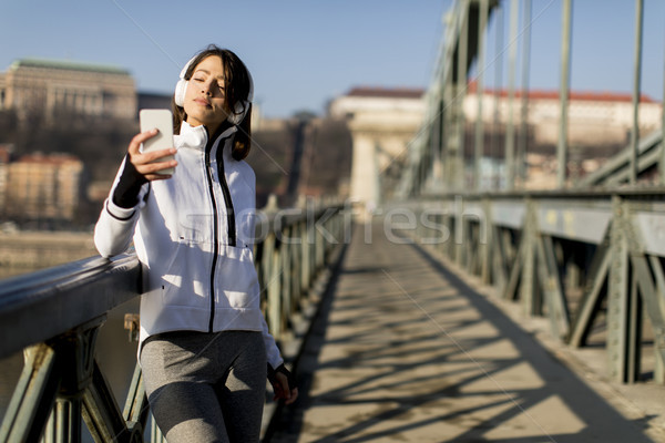 Woman on the bridge making a pause after the exercise Stock photo © boggy