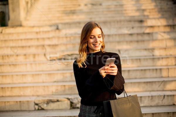 Fiatal nő bevásárlószatyor mobiltelefon szabadtér portré telefon Stock fotó © boggy