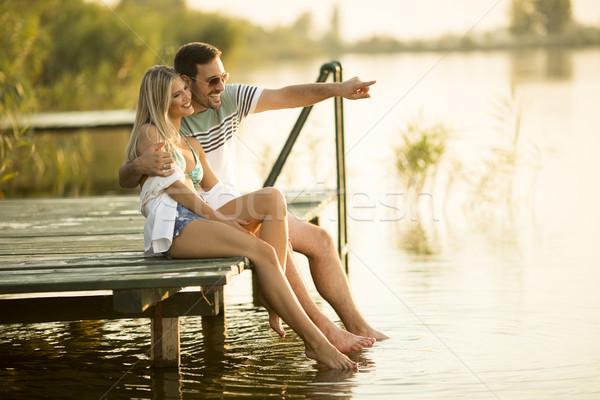Romantique couple séance bois pier lac Photo stock © boggy