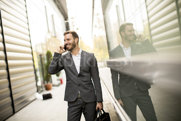 Young successful man  executive businessman using his mobile cel Stock photo © boggy