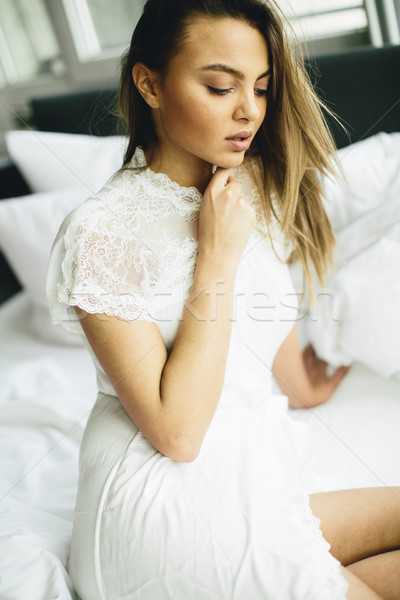 Fiatal nő ágy fehér vászon lány haj Stock fotó © boggy