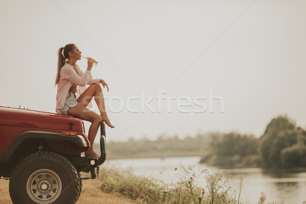 Young woman sits on a car hood and drinks refreshment Stock photo © boggy