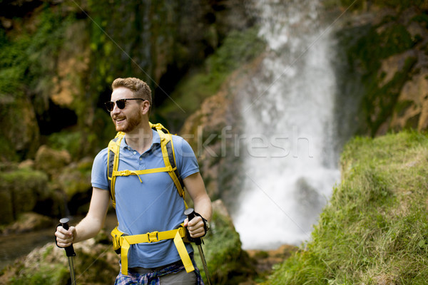 Stock photo: Young hiker stopped beside a mountain waterfall to rest