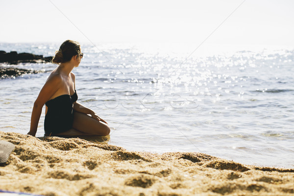 Young women in bathing suit sitting in the sand by the sea Stock photo © boggy