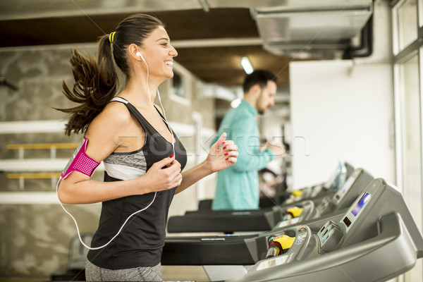 Young woman running on the treadmill and listening to music at t Stock photo © boggy
