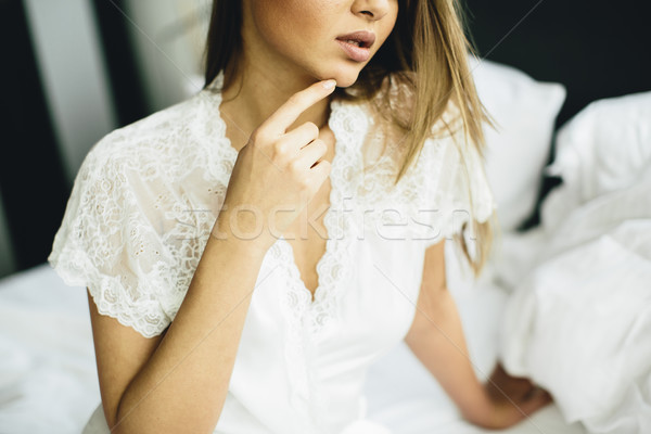 Young woman sits on a bed with white linen Stock photo © boggy