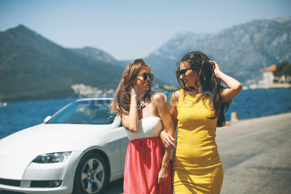Two pretty young women by white cabriolet car Stock photo © boggy