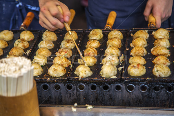 Takoyaki being grilled at a street food stall in Osaka, Japan Stock photo © boggy