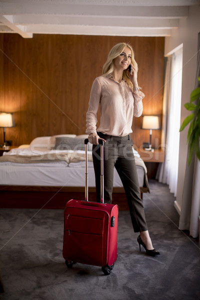 Young woman with luggage in hotels room Stock photo © boggy