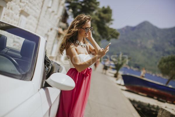 Mulher jovem telefone móvel em pé cabriolé carro quente Foto stock © boggy