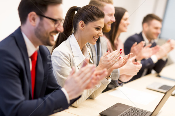Happy smiling business team clapping hands during a meeting Stock photo © boggy