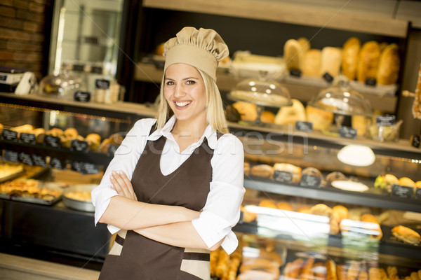 Beautiful young woman smiling confidently posing in her baker sh Stock photo © boggy