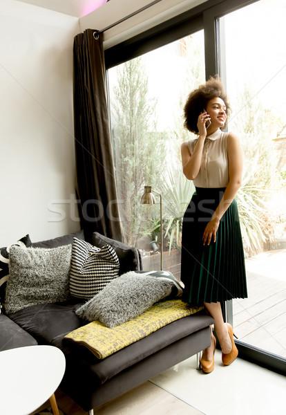 вьющиеся волосы мобильного телефона дома довольно женщину Сток-фото © boggy