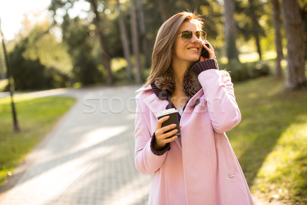Young woman with coffee to go in hand using a mobile phone Stock photo © boggy