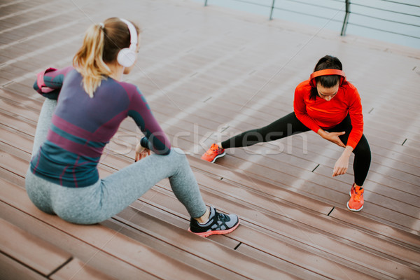 Young woman exercising with a personal trainer outside Stock photo © boggy