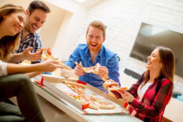 Groep jonge vrienden eten pizza home Stockfoto © boggy