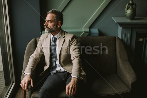 Jóképű idős üzletember ül lobbi portré Stock fotó © boggy
