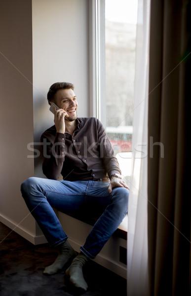 ストックフォト: 若い男 · 携帯電話 · ルーム · ハンサム · 笑顔 · 携帯