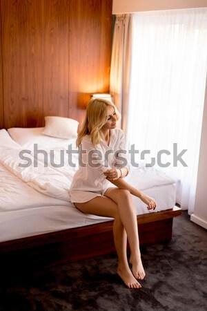 Jovem mulher loira sessão cama quarto Foto stock © boggy