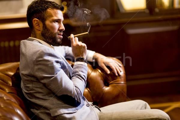 Bel homme séance cuir canapé fumer cigare Photo stock © boggy