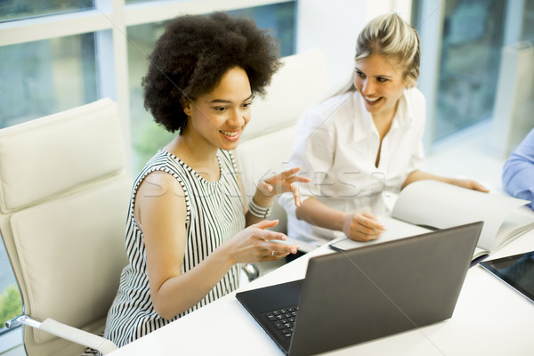 Happy african american and blonde  businesswomen with laptop com Stock photo © boggy