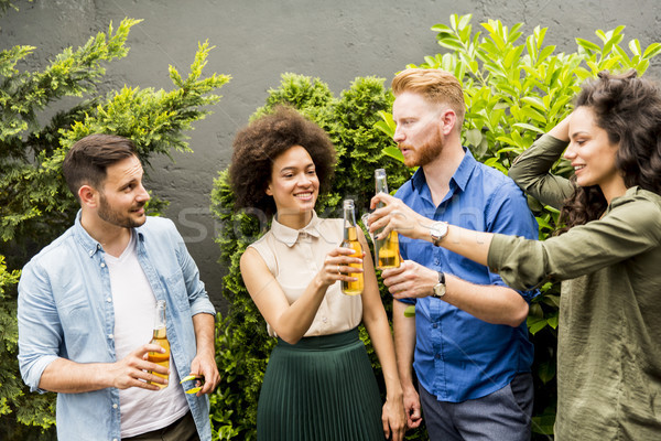 Young smiling people stand outside and toast with cider in the h Stock photo © boggy