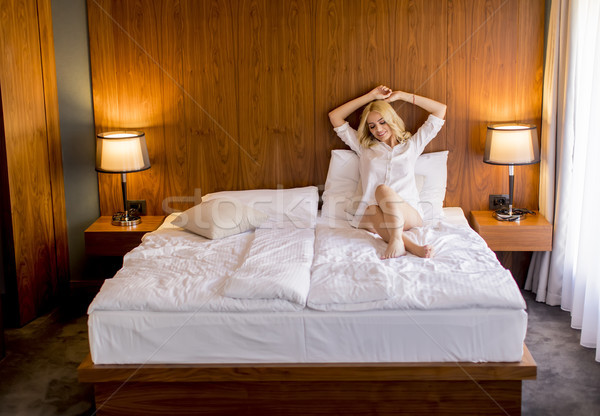 Young blonde woman on the bed looks happy and satisfied Stock photo © boggy