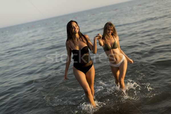 Two young women in swimwear  having fun in the sea at sunset Stock photo © boggy