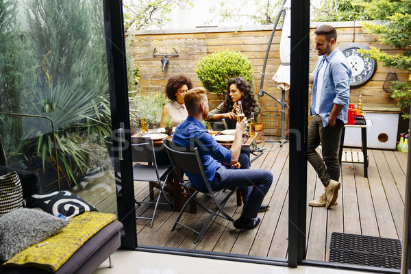 Friends grilling food and enjoying barbecue party outdoors Stock photo © boggy