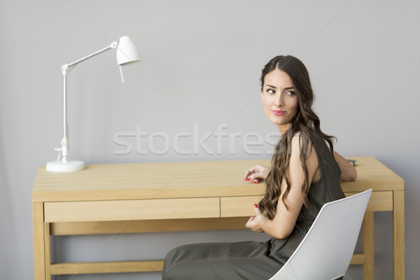 Woman sitting by table in the room Stock photo © boggy