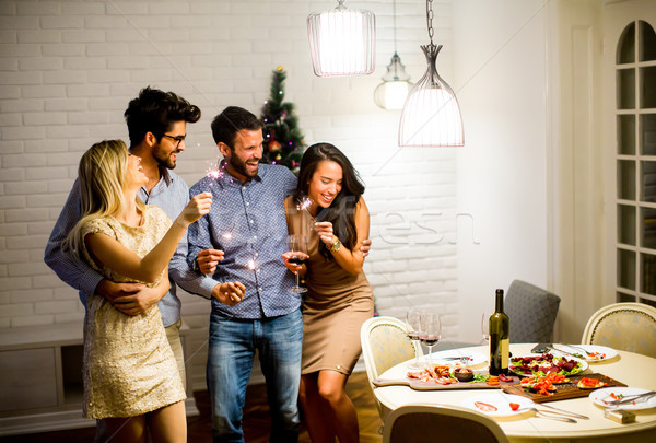 Cheerful women and men celebrating New Year eve with sparkles an Stock photo © boggy