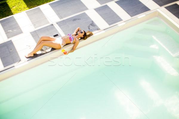 Mulher jovem piscina espreguiçadeira verão dia água Foto stock © boggy